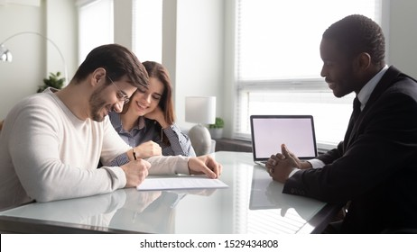 Side view happy young family couple signing contract, satisfied with first big purchase, glad to receive bank credit loan mortgage. Smiling african american insurer meeting with positive clients.