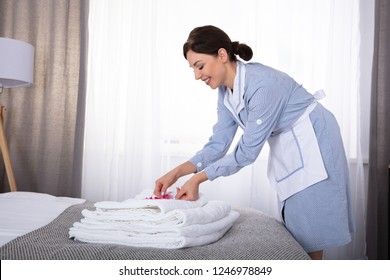 Side View Of A Happy Young Housemaid Placing Flowers On Stack Of Towels Over Bed
