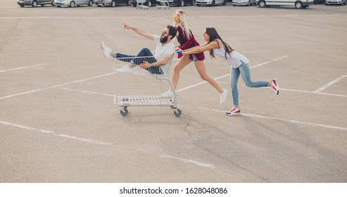 Side view of happy young ladies pushing shopping trolley with bearded man while having fun on asphalt parking lot near supermarket