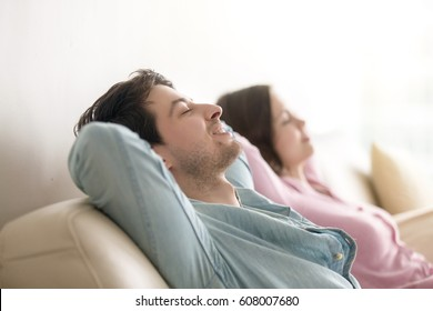 Side view of happy young man and woman enjoying sitting on sofa at home, relaxing with eyes closed, resting hands behind the head, breathing, dreaming of vacation, imagining, leisure lazy day