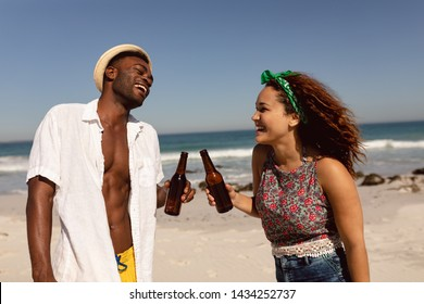 Side view of happy young Mixed-race couple with beer bottle having fun on beach in the sunshine