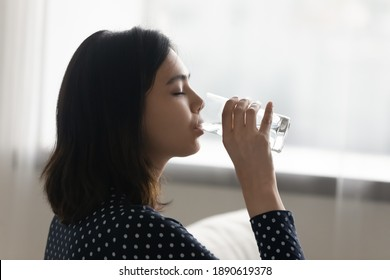 Side view happy young multiracial asian korean woman drinking cool distilled water from glass, keeping dietary lifestyle, enjoying morning healthcare habit, hydrating organism with fresh aqua at home. - Shutterstock ID 1890619378