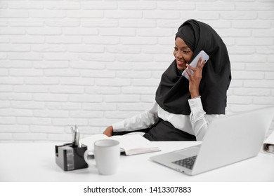 Side view of happy young woman in hijab sitting at table in office and talking by phone. Muslim female relaxing during break at job and laughing. Concept of religion and communication.