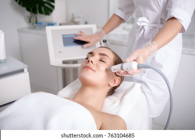 Side view of happy young woman getting cavitation rejuvenating skin treatment at spa. She is lying on massage table and smiling. Beautician is touching monitor screen while holding tool near female