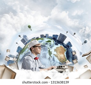 Side view of hard-working man writer using typing machine while sitting at the table with flying books and Earth globe among cloudy skyscape on background. Elements of this image furnished by NASA