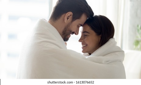Side view head shot close up young bonding family couple covered in warm cozy blanket touching foreheads, enjoying intimate tender moment. Happy married spouse spending sweet morning time together.