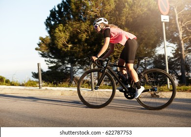 Side view of healthy athletic European woman cycling alone in helmet and sunglasses, riding bike at countryside, spending her active summer weekend, feeling free of exhausting urban life and rhythm
