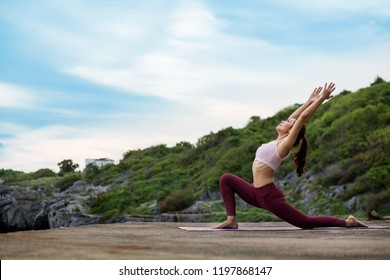 Side view of healthy women practicing yoga. standing in Warrior I pose.asana Anjaneyasana - low crescent lunge pose. in surya namaskar.     beautiful landscape view sky on evening