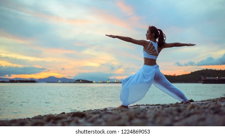 Side view of healthy women practicing yoga. standing near sea. exercise virabhadrasana.  warrior ll pose. . enjoying sea view with morning, concept for exercising, copy space for text