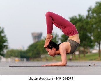 Side view of healthy women in sportswear practicing yoga outdoor. Doing advanced inversion and arm balance Scorpion Handstand, asana Scorpion Pose Vrischikasana forearm stand, full length portrait.