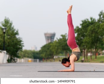 Side view of healthy women in sportswear, red pants and top practicing yoga outdoor, doing handstand exercise on yoga mat salamba sirsasana pose, full length portrait.