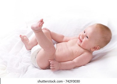 Side view of high key studio shot of happy 3 to 4 month old baby boy laying on his back smiling