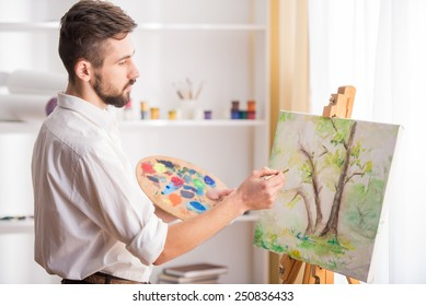 Side view of highly gifted painter while he is painting his picture.