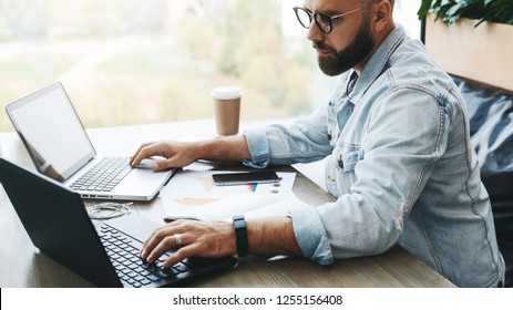 Side view. Hipster bearded businessman sits in cafe, modern office, works on two laptops. Freelancer works remotely. Student is preparing for exams. Startup. Online marketing, education for adult.