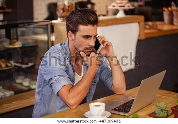 Side view of hipster man working at cafe