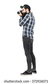 Side view of hipster in plaid shirt and baseball cap taking photo with dslr camera. Full body length portrait isolated over white studio background.