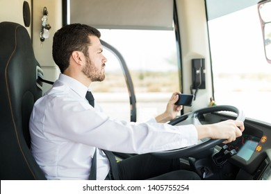Side view of Hispanic bus driver with mobile phone driving with GPS navigator