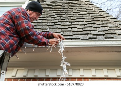 Side view of a home owner on a ladder hanging lights on the outside of his house