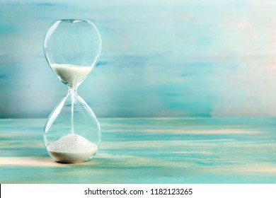 A side view of an hourglass with falling sand, on a teal background with copy space