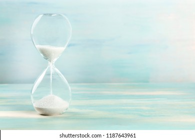 A side view of an hourglass with falling sand, on a teal background with copy space, slightly toned image