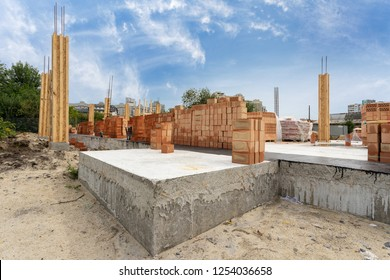 Side view of house support elements and new brick wall. Beginning of the construction residential building with wooden and concrete column formwork against blue sky