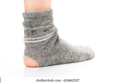Side view of human foot dressed in old worn out dirty gray sock with holes isolated on a white background. Detailed closeup studio shot.