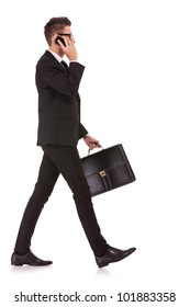 side view of a hurrying business man talking on the mobile phone on white background