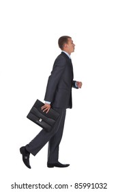 side view of a hurrying business man with briefcase in hand over white background