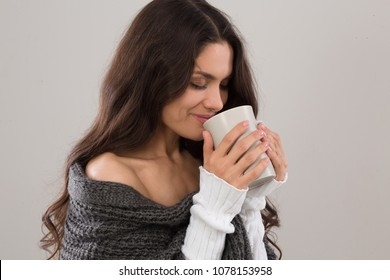 Side view iamge of brunette woman having cup of coffee. Wearing gray cardigan. Mid age woman over 35 years old beauty concept.