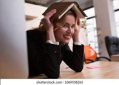 Side view iamge of young businesswoman having book on head.