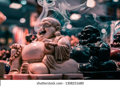 Side view of the iconic Smoking Buddha. Macro shot close up of smoke floating out of the mouth. Incense stick holder, Indian religious symbol, yoga and meditation concept. Black and white models.