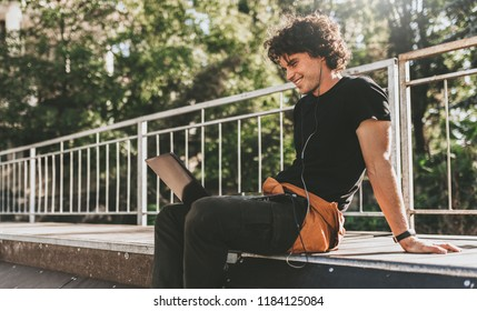 Side view image of cheerful Caucasian male with curly hair using laptop computer and smiling while sitting on the pavement. Young freelance business man working outside.