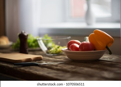 Side view image of different vegetables in spot on wooden table. Healthy lifestyle concept.