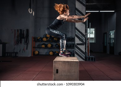 Side view image of fit young woman doing a box jump exercise. Muscular woman doing a box squat at the Crossfit  gym