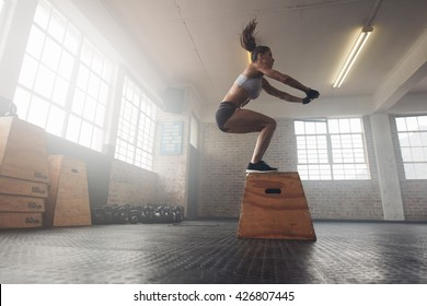 Side view image of fit young woman doing a box jump exercise. Muscular woman doing a box squat at the gym