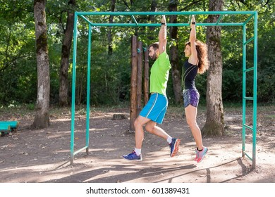 Side view image of a young couple working out together using exercise equipment in the city park. They are wearing fitness trackers