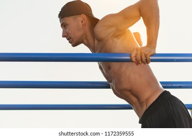 Side view image of young fitness muscular man doing exercises on horizontal crossbar outdoors. Handsome athletic shirtless male training hard at afternoon outside, sportsman working out outside.