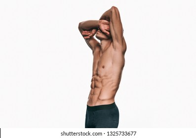 Side view image of young handsome male model in black underwear showing his abdominal torso on white studio wall. Sporty handsome athletic man with sexy abdomen isolated on white background. Healthy