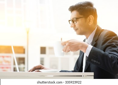Side view of Indian businessman at cafeteria, having a cup of coffee and using laptop computer.