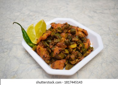 Side view of Indian curry Aloo bhindi or Alu bhindi sabzi home made, cooked at home with Indian masala garnished with fresh green chilly and lemon. Indian food cuisine side dish
