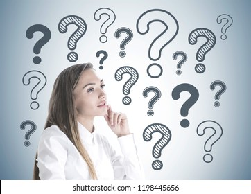 Side view of inspired young businesswoman with long fair hair wearing white shirt thinking about business challenge. Gray wall background with many question marks