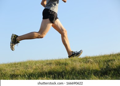 Side view of a jogger legs running on the grass with the horizon in the background