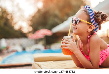 Side view of joyful kid in vivid pink swimsuit sunglasses and headband with glass of tasty fresh drink looking away, and dreaming while laying on sofa against blurred swimming pool