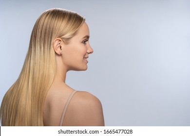 Side view of a joyful young lady with long loose hair looking in front of her