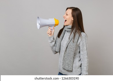 Side view of joyful young woman in gray sweater, scarf scream in megaphone isolated on grey wall background. Healthy fashion lifestyle people sincere emotions, cold season concept. Mock up copy space