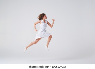 Side view of joyous girl in dress jumping up in air over background in studio