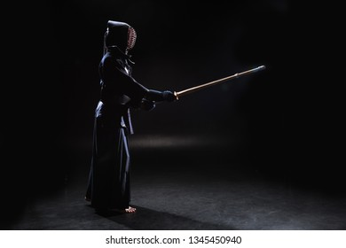 Side view of kendo fighter in armor practicing with bamboo sword on black