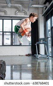 side view of kid boy jumping at fitness studio, children sport concept