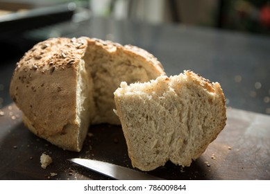 side view of knife and freshly baked Rustic home-made bread with sunflower and sesame seeds on a cutting board with a slice and warm air that evaporates from a slice, food closeup.
