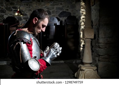 Side View of Knight Kneeling on His Knees Praying Before Battle